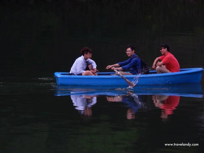 Three boys enjoy a boating session in a lake near the Arashiyama Bamboo Grove