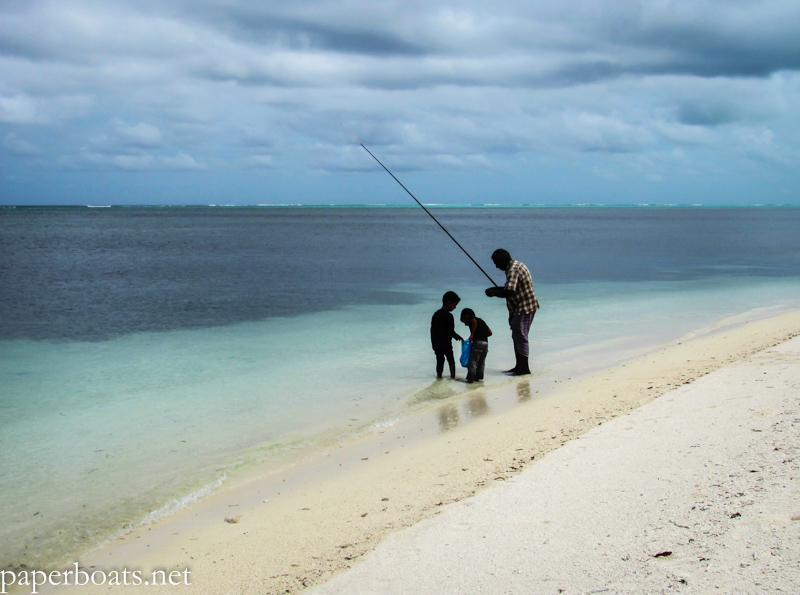 Father and sons fish at a beach in Maafushi