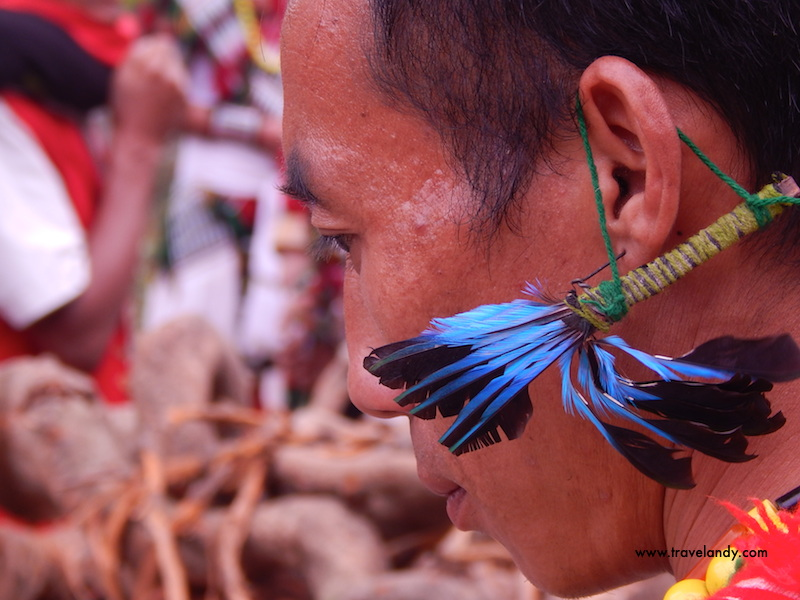 A tribal man sports a colourful earring made of bird features